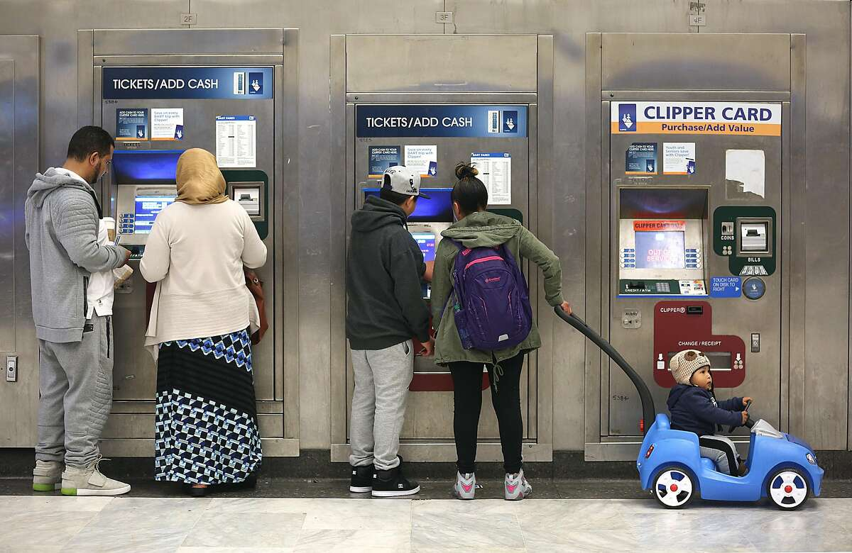 Bart commuters including Francisco Mendoza (middle) with her sister Carmelina Mendoza (middle right) with her 1 year old child Michael (right) buy tickets to go to Oakland at the Civic Center station on Tuesday, April 10, 2018, in San Francisco, Calif.