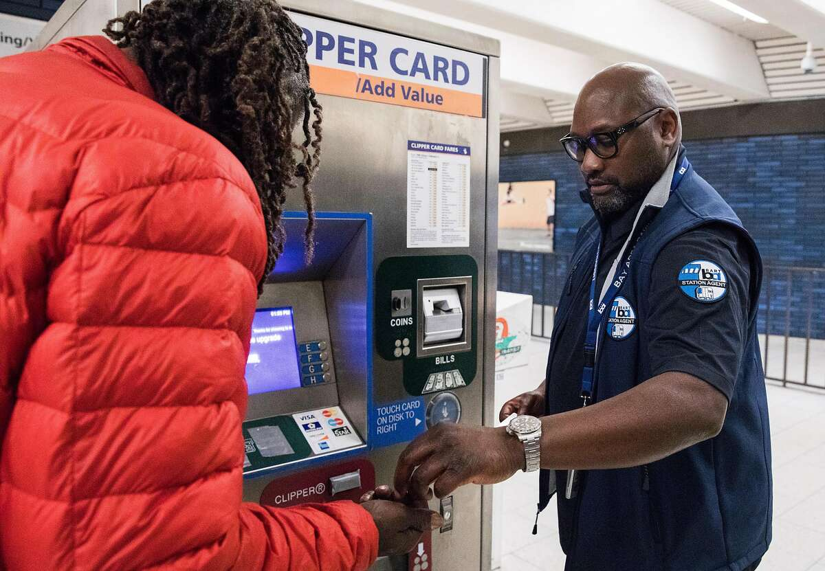 BART Station Agent William Cromartie helps a passenger add fare to their Clipper Card while working the information booth at the 19th Street BART Station in Oakland, Calif. Tuesday, July 2, 2019.