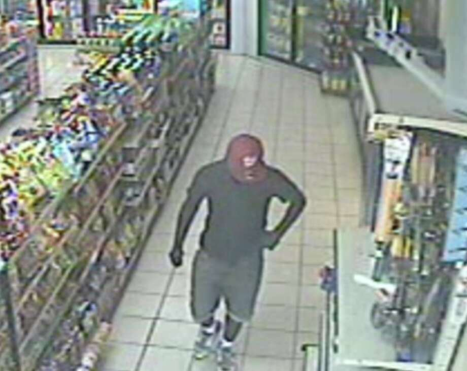 Surveillance video shows a man suspected of killing a convenience store clerk strolling around the shop moments before the botched robbery Sunday, Aug. 4, 2019. Photo: Houston Chronicle