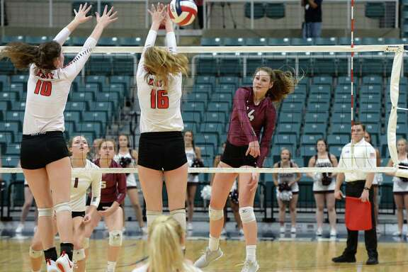 Danyle Courtley (14) of Cinco Ranch attempts a kill shot past Allison Parks (10) and Maddie Waak (16) of Katy in the second set of a Class 6A - III Regional Quarterfinal playoff volleyball match between the Cinco Ranch Cougars and the Katy Tigers on Monday, November 5, 2018 at the Leonard Merrell Center, Katy, TX.
