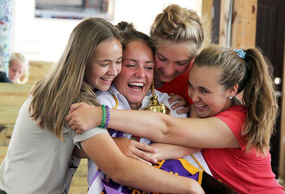 Swarmed by family and friends, Maddie Laskowski (center) is greeted with hugs and smiles as she holds onto her championship trophy. Laskowski was named the Junior Livestock Association Sweepstakes winner on Saturday at the Huron Community Fair. Photo: Andrew Mullin/Huron Daily Tribune