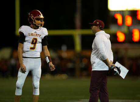 Liberty quarterback Jay Butterfield (9) and Liberty head coach Ryan Partridge confer during a timeout in the second quarter of a high school football game against Pittsburg, on Friday, Oct. 19, 2018 in Pittsburg, Calif.