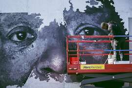 The artist Sean Michael Warren works on his mural that honors powerful black women and their resilience at the Dr. Maya Angelou Community High School in Los Angeles, May 2019. The mural is one of 28 works honoring Angelou that are now featured on the school's grounds as part of a recent public arts project. (Carlos Gonzalez/The New York Times)