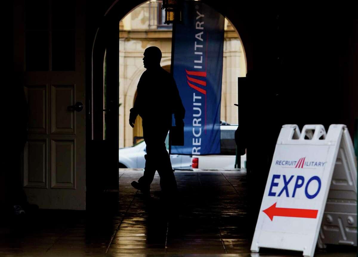 The silhouette of a job seeker is seen entering the Recruit Military veteran job fair in San Diego, Calif.