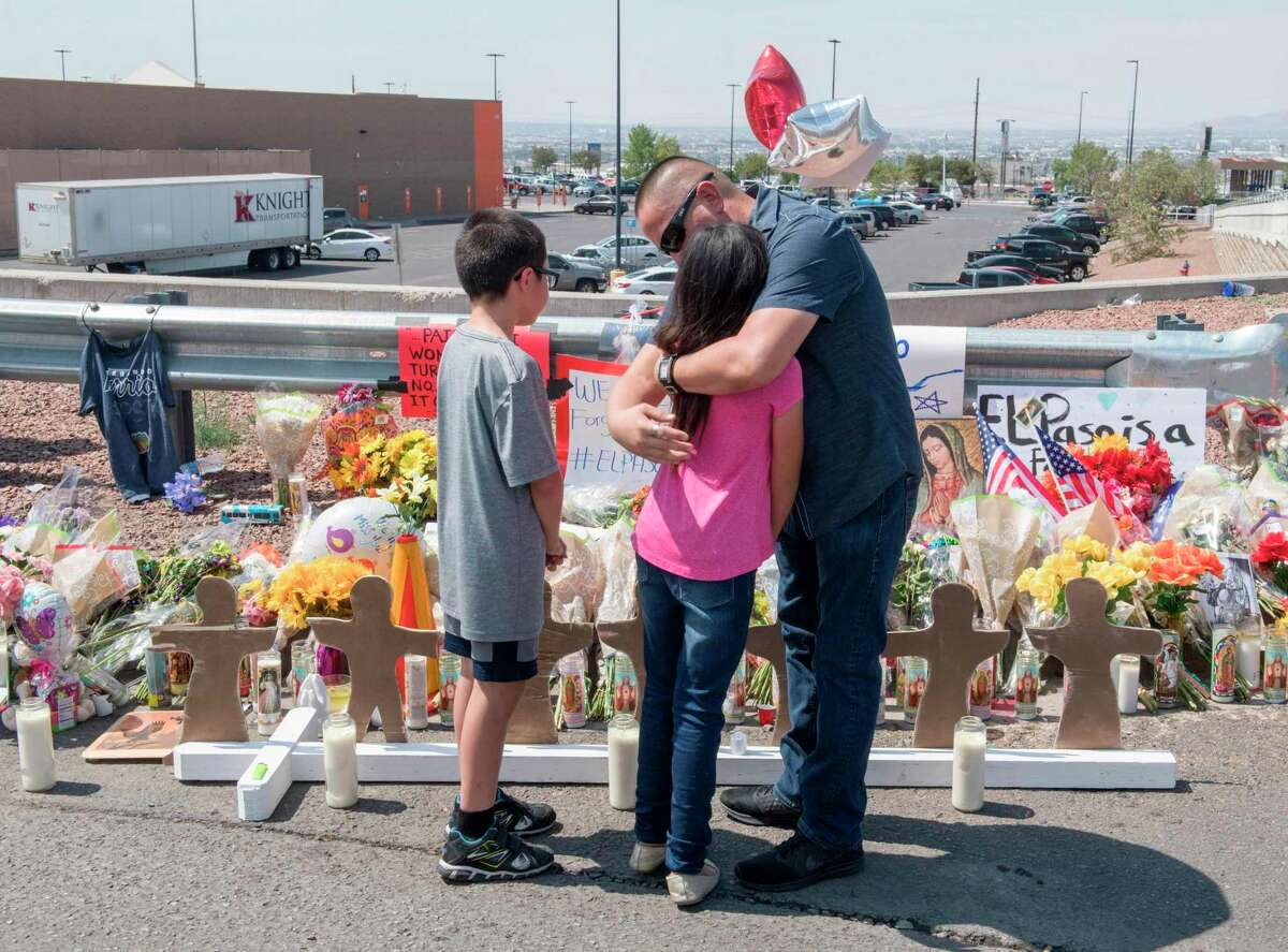 Members of the Soto family embrace beside a makeshift memorial after the shooting that left 22 people dead at the Cielo Vista Mall WalMart in El Paso, Texas, on August 5, 2019. - US President Donald Trump on Monday urged Republicans and Democrats to agree on tighter gun control and suggested legislation could be linked to immigration reform after two shootings left 30 people dead and sparked accusations that his rhetoric was part of the problem.