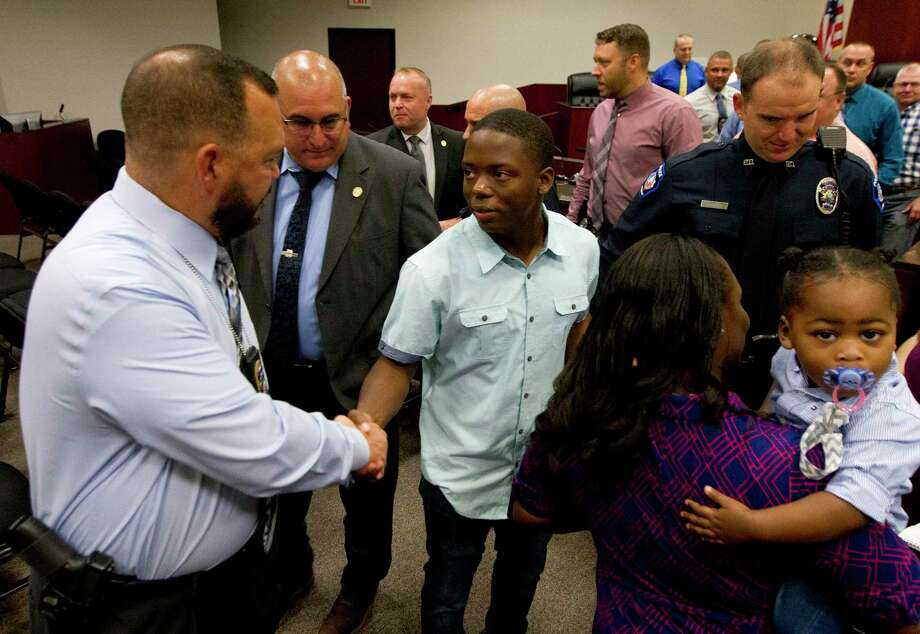 Grant Brown, 19, shakes hands with members of law enforcement after he helped save his six-year-old neighbor Mason Lineman from a July 21 pit bull attack at their home in the Deer Trail II subdivision during the council's meeting at Conroe Tower, Monday, Aug. 5, 2019, in Conroe. Photo: Jason Fochtman, Houston Chronicle / Staff Photographer / Houston Chronicle