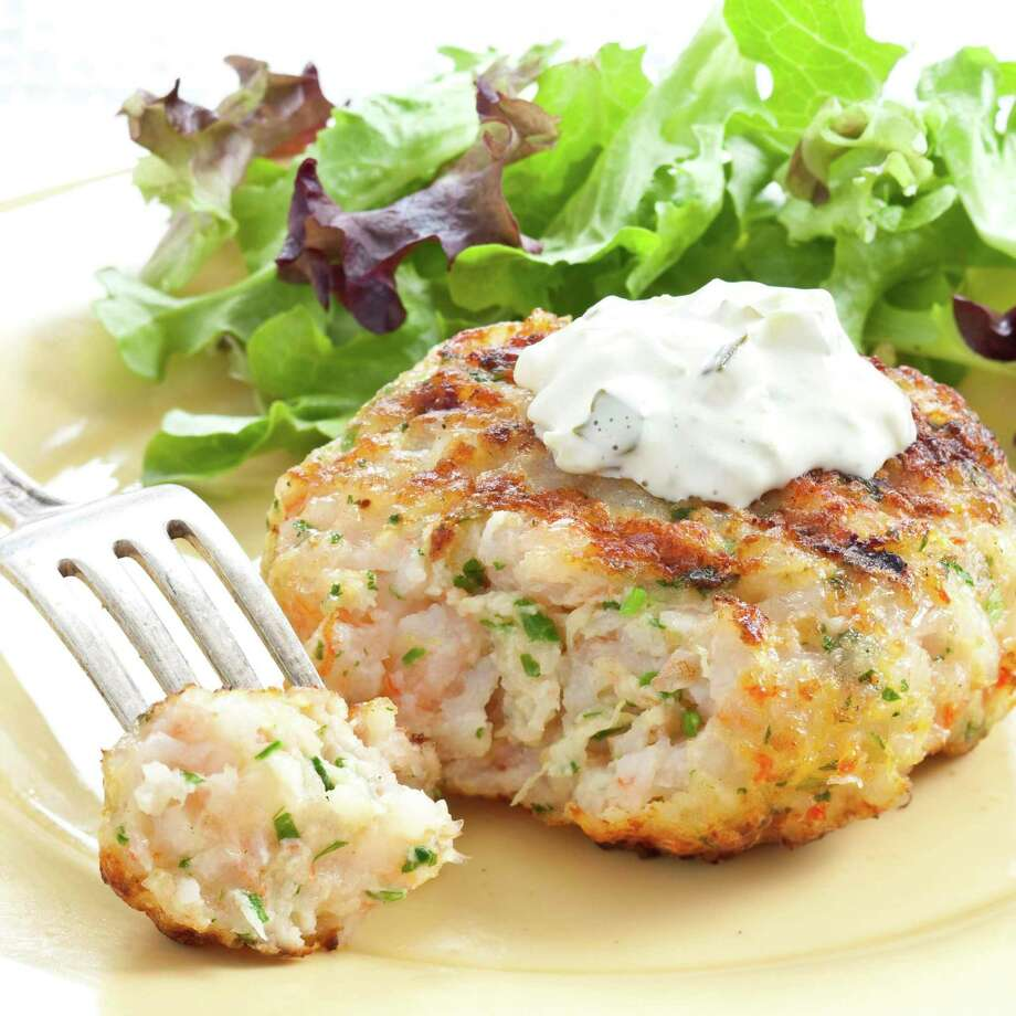 """This undated photo provided by America's Test Kitchen in July 2019 shows Grilled Southern Shrimp Burgers in Brookline, Mass. This recipe appears in the cookbook """"Master of the Grill."""" (Daniel J. van Ackere/America's Test Kitchen via AP) Photo: Daniel J. Van Ackere / Daniel J. Van Ackere / America's Test Kitchen / © 2009 Boston Common Press, DBA America's Test Kitchen. All Rights Reserved."""