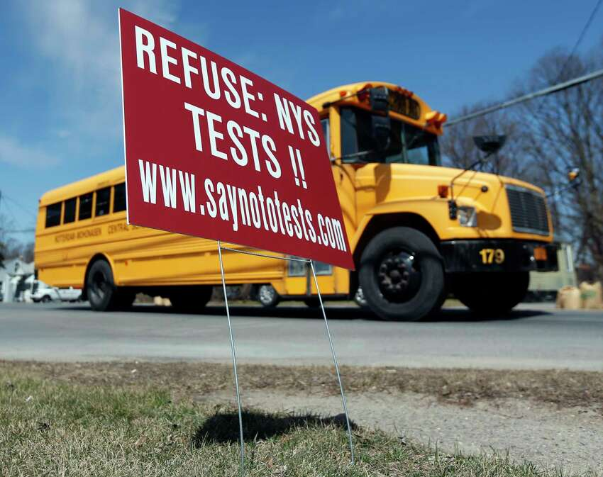 FILE - This April 13, 2015 file photo shows a school bus passing a sign encouraging parents to refuse that their children take state tests on in Rotterdam, N.Y. New York state is re-thinking its requirements for a high school diploma, including the make-or-break Regents exams that have been around since the 1800s. (AP Photo/Mike Groll, File)