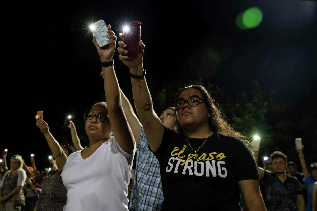 Karina Cardoso and Linda Nevarez hold their cellphone flashlights up during a vigil Sunday at Ponder Park in honor to the victims of a mass shooting occurred in Walmart Saturday in El Paso, Texas.