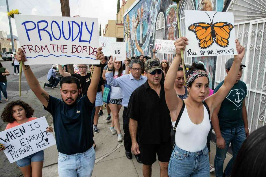 People march in silence Sunday, Aug. 4, 2019, in El Paso, Texas, holding sunflowers and signs to honor the victims of the mass shooting that occurred in Walmart on Saturday, Aug. 3, 2019. (Lola Gomez/Austin American-Statesman via AP) Photo: Lola Gomez / Associated Press / Austin America-Statesman