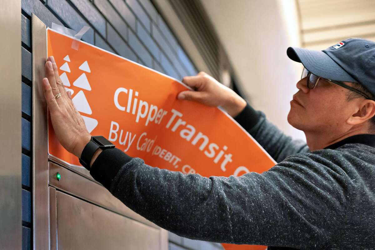 A BART automatic fare collection tech installs signage on one of the converted Clipper card machines at the 19th Street BART station on Monday, Aug. 5, 2019, in Oakland, CA.