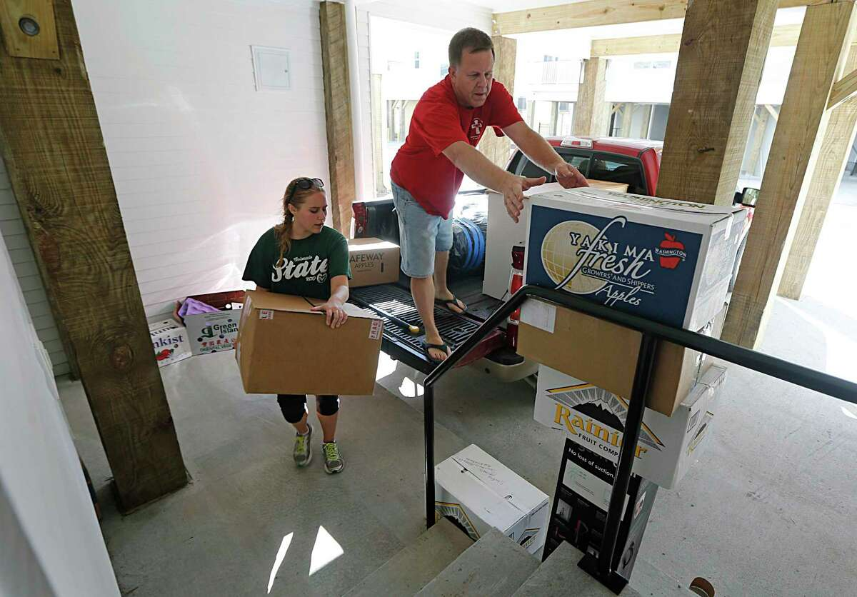 Katie Schmitz left, with the help of her father Terry Schmitz right, moves into the Cedars at Carver Park mixed income housing development in 2015.