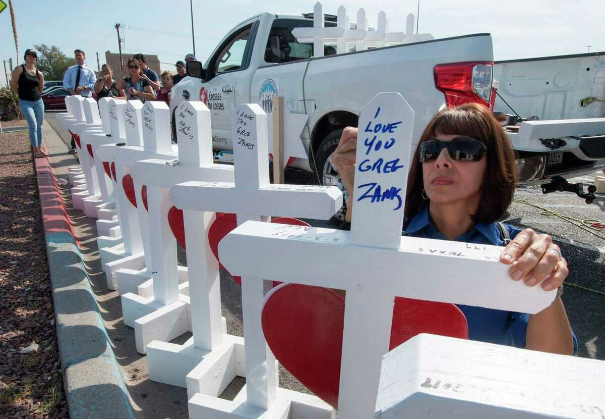 Members of the group Crosses for Losses group put up memorial crosses, one for each victim of the Walmart shooting in El Paso, Texas.