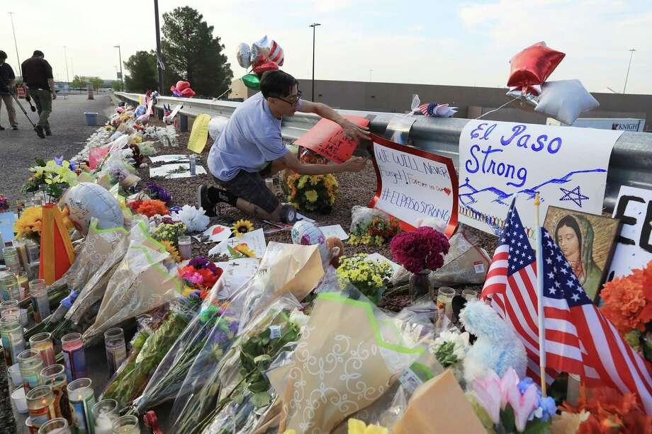 René Romo agrega un cartel a un monumento improvisado en la tienda Walmart en El Paso, Texas, el lunes 5 de agosto de 2019, dos días después de que un hombre armado abrió fuego dentro de la tienda, matando a 22 personas e hiriendo a docenas más. Photo: Jim Wilson /NYT / NYTNS