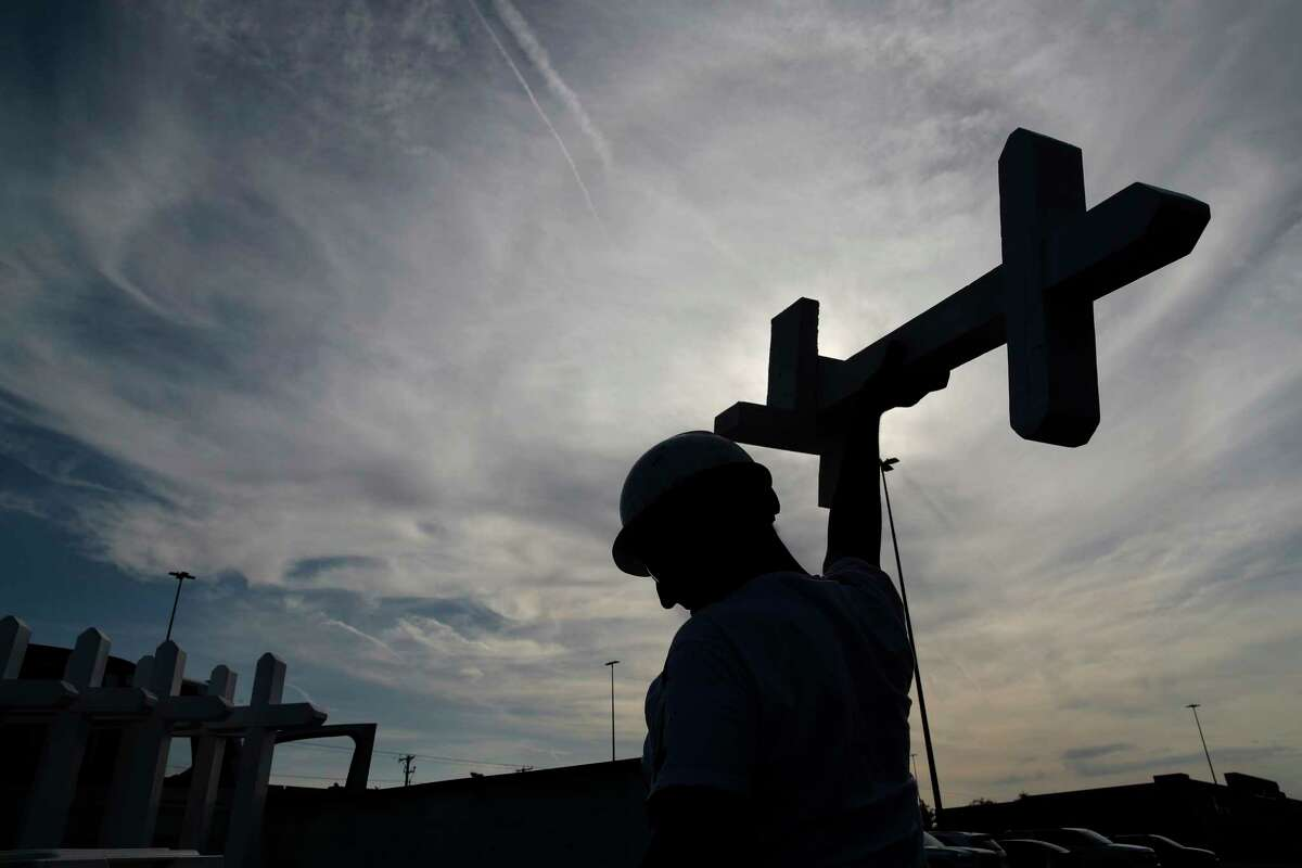 Greg Zanis prepares crosses to place at a makeshift memorial for victims of a mass shooting at a shopping complex Monday, Aug. 5, 2019, in El Paso, Texas. (AP Photo/John Locher)