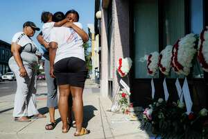 """Family members of slain mass shooting victim Thomas """"TJ"""" McNichols, from left, Donna Johnson, aunt, and sisters Jamila and Finesse McNichols, mourn beside a memorial near the scene of the shooting Monday, Aug. 5, 2019, in Dayton, Ohio. (AP Photo/John Minchillo)"""