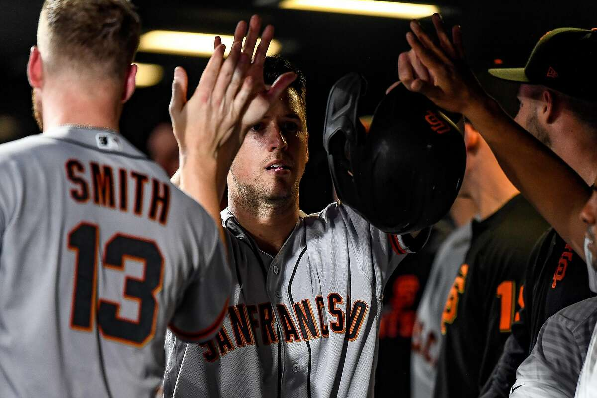 DENVER, CO - JULY 16: Buster Posey #28 of the San Francisco Giants celebrates scoring a go-ahead run in the 10th inning at Coors Field on July 16, 2019 in Denver, Colorado. (Photo by Dustin Bradford/Getty Images)