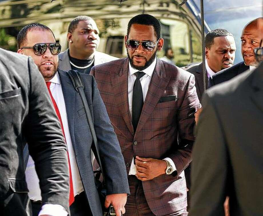 R&B singer R. Kelly (center) arrives June 26 at Chicago's Leighton Criminal Court building for an arraignment on sex-related felonies in Chicago. The singer was charged Monday in Minnesota with two counts of prostitution and solicitation involving a girl under 18. Photo: Amr Alfiky | Associated Press