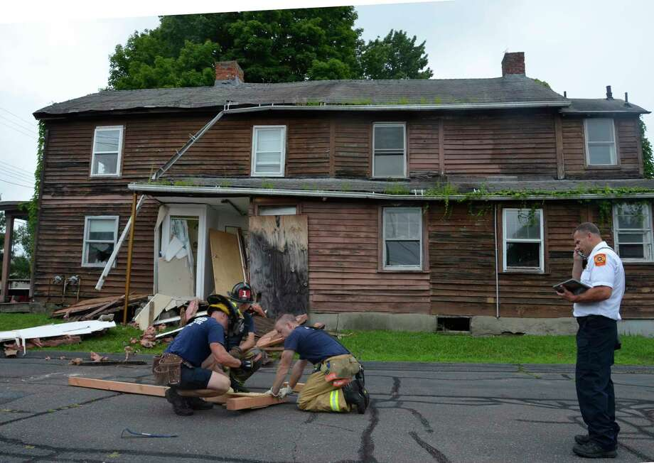 Firefighters shore up an empty house at 183 Buckingham Avenue, Milford, Conn., on Tuesday, Aug. 6, after the building was struck by a car. Photo: Jill Dion / Hearst Connecticut Media