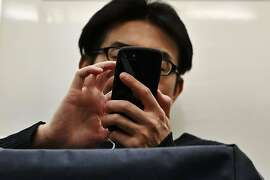 (FILES) In this file photo taken on April 29, 2019 A man uses his smartphone on the train at night in Tokyo. - Optimize battery autonomy, limit the obsolescence of phones, moderate the use of servers: the design of less energy-hungry software is finding increasing interest among digital players. (Photo by Charly TRIBALLEAU / AFP)CHARLY TRIBALLEAU/AFP/Getty Images