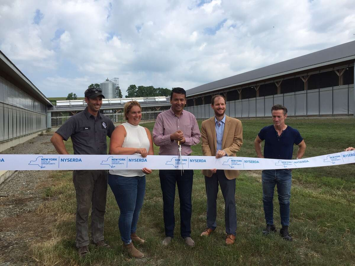 NYSERDA held a ribbon-cutting at the Copses Farms in Valley Falls on Tuesday for a new solar array made with mirrors built by a company called Skyven Technologies that produces industrial steam for the farm's dairy cow operation. Pictured from left to right is Eric Mayer and Maureen Mayer, owners of Copses Farms, Arun Gupta, CEO and founder of Skyven, John Lochner, vice president of technology and business innovation at NYSERDA, and Terry Moag, CEO and founder of The Radiant Store.