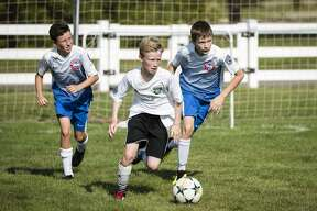 Midland Fusion's Izaac Ringgould (white) kicks the ball down the field, followed by Lucas Duran and Owen Senkowski of the Tri-County Nationals during the Inaugural Bailee Mantei Foundation 3v3 Soccer Tournament at the Midland Soccer Complex on Saturday, July 3, 2019. Proceeds from the event will be put into the foundation's fund for annual scholarships in Bailee Mantei's memory. (Danielle McGrew Tenbusch/for the Daily News)