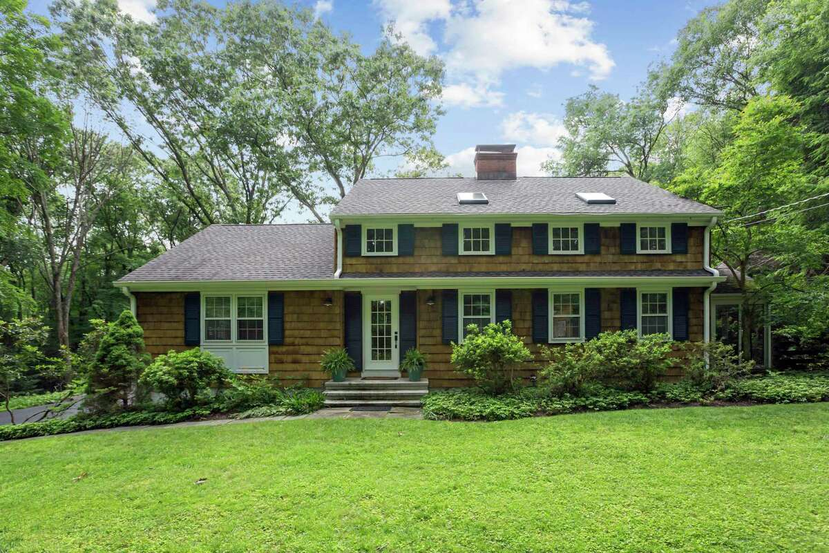 The natural wood-colored colonial house at 45 Norton Road sits on a 3.12-acre sanctuary-like setting in the Aspetuck section of Easton.