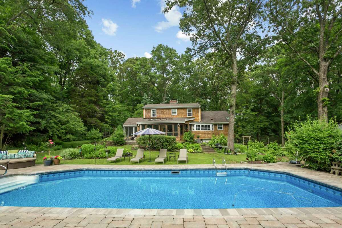 In the sizable backyard there is a heated in-ground vinyl swimming pool, patio, wood deck, hot tub, fire pit, outdoor shower, and professionally landscaped gardens.
