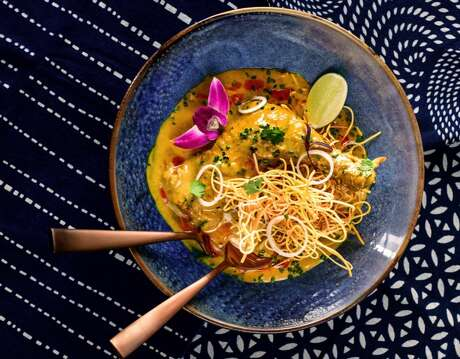 The Khao Soi, a Northern Thai yellow chicken curry, is served over soft egg noodles with crispy noodles on top.