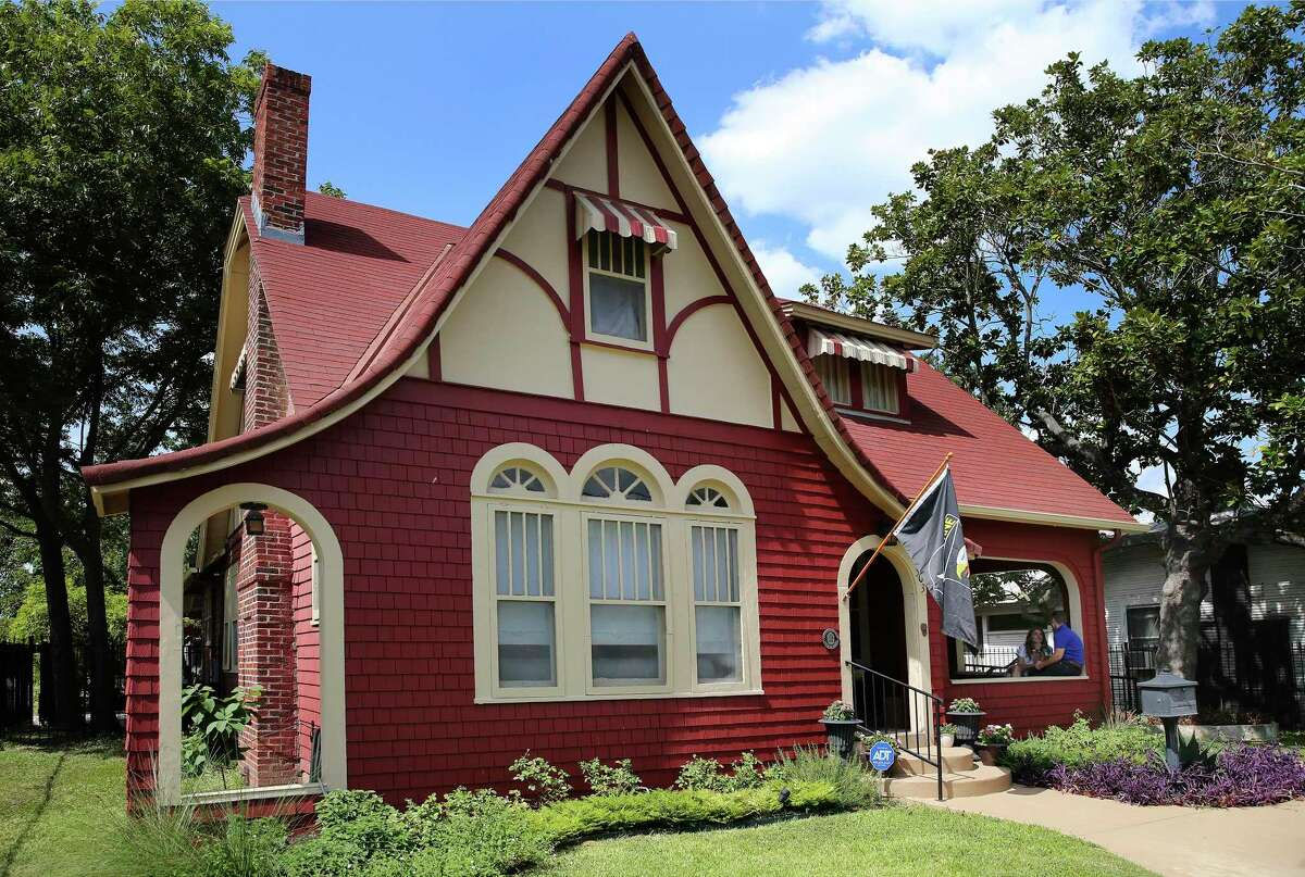 With wood shake siding painted red on the lower walls and stucco and trim in the gables Rachel and Larkin O'Hern's Tobin Hill home is in the English Cottage style with an exaggerated, fairy tale roofline.