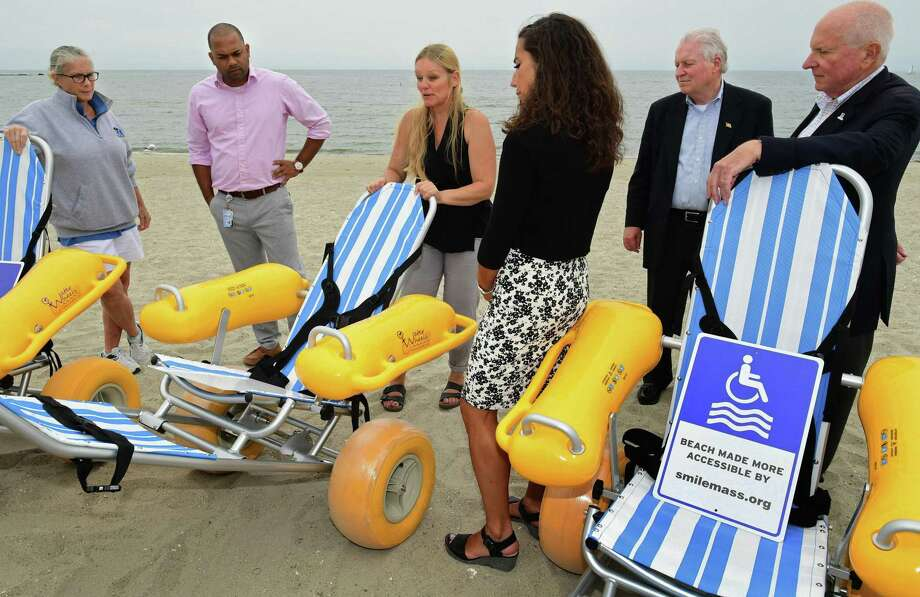 SMILE Mass (Small Miracles in Life Exist) founder Lotte Diomede, center, donates floating beach wheelchairs to Norwalk Recreation and Parks Aquatic Director Pat Raila, Recreation and Parks Director Nick Roberts, Westport Parks and Recreation Director Jen Fava and First Selectman Jim Marpe right, and Fairfield First Selectman Mike Tetreau, second from right, during a press conference Tuesday, August 6, 2019 , at Compo Beach in Westport, Conn. SMILE Mass has donated over 130 of the floating beach wheelchair throughout New England and Tuesday's donations to Norwalk, Westport, and Fairfield, were the first in Connecticut. The floatable wheelchairs, which resemble beach recliners, have shock-absorbing wheels that maneuver easily over sandy terrain. Photo: Erik Trautmann / Hearst Connecticut Media / Norwalk Hour