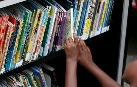 Second Ward and area children look though books at the Houston Public Library Bookmobile Thursday, July 5, 2018, in Houston. The Flores Neighborhood Library is one of six Houston Public Library branches that has been closed since Harvey damaged it last August.