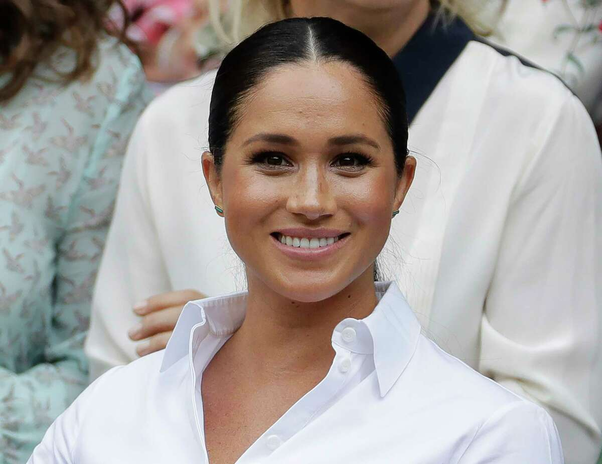 FILE - In this July 13, 2019 file photo, Kate, Meghan, Duchess of Sussex smiles while sitting in the Royal Box on Centre Court to watch the women's singles final match between Serena Williams, of the United States, and Romania's Simona Halep on at the Wimbledon Tennis Championships in London. Meghan has guest edited the September issue of British Vogue with the theme