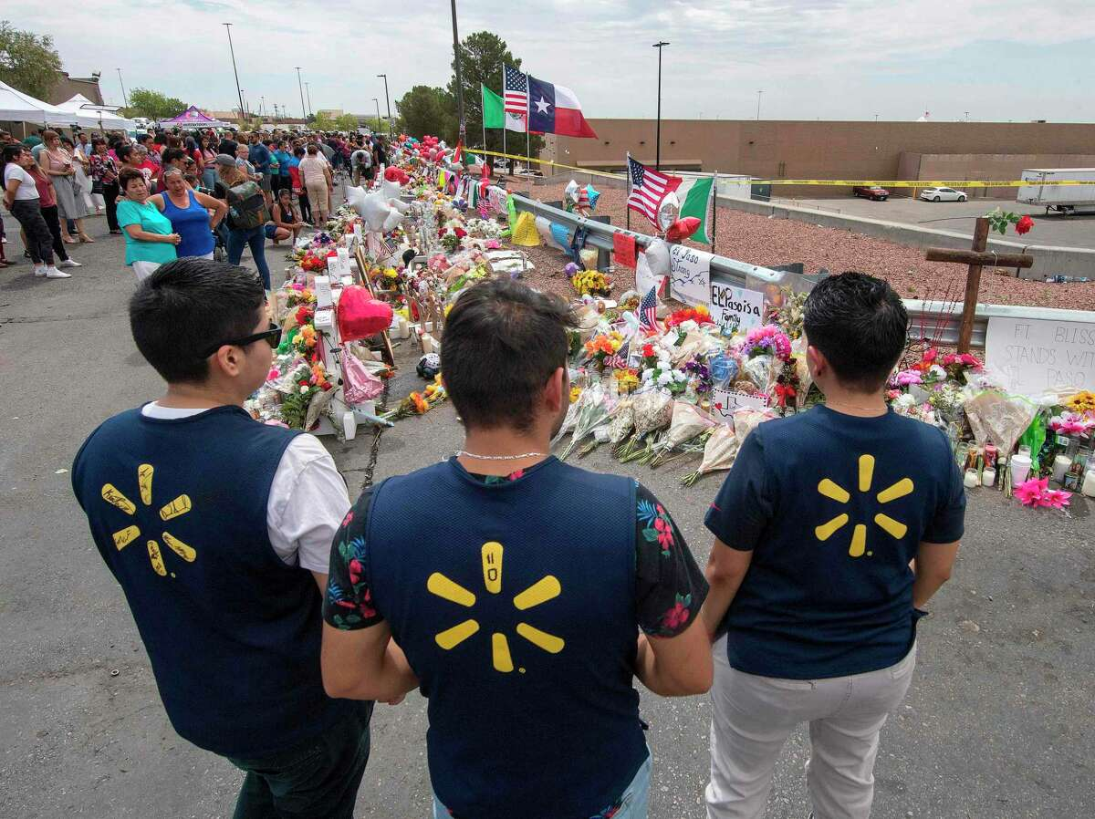Walmart employees pay their respects at a makeshift memorial for the shooting victims, at the Cielo Vista Mall Walmart in El Paso, Texas, on August 6, 2019. - The August 3 shooting left 22 people dead. US President Donald Trump will visit the Texan border city August 7, and will also travel to Dayton, Ohio where a second mass shooting early August 4 left another nine dead. (Photo by Mark RALSTON / AFP)MARK RALSTON/AFP/Getty Images