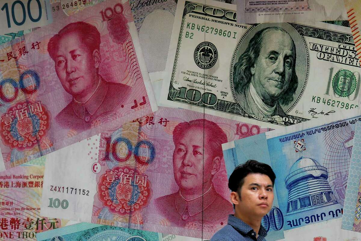 A man walks past a money exchange shop decorated with different banknotes at Central, a business district in Hong Kong, Tuesday, Aug. 6, 2019. China's yuan fell further Tuesday against the U.S. dollar, fueling fears about increasing global damage from Beijing's trade war with President Donald Trump. (AP Photo/Kin Cheung)