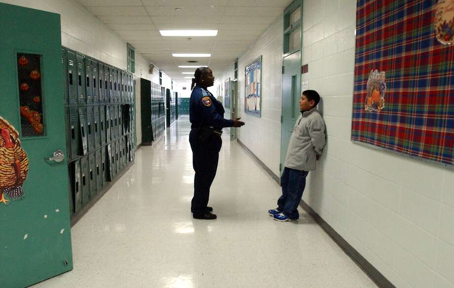 Officer Rogena Reed in 2002, talking with 7th grader Robert Garcia in a school hallway in Edgewood ISD.  (Robert McLeroy/Staff) Photo: ROBERT MCLEROY /SAN ANTONIO EXPRESS-NEWS / SAN ANTONIO EXPRESS-NEWS