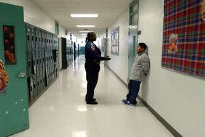Officer Rogena Reed in 2002, talking with 7th grader Robert Garcia in a school hallway in Edgewood ISD.  (Robert McLeroy/Staff)