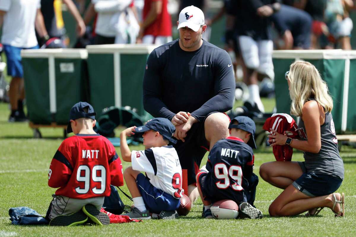 Houston Texans defensive end J.J. Watt sits down to talk to a group of young kids following a joint training camp practice with the Green Bay Packers on Tuesday, Aug. 6, 2019, in Green Bay, Wis.