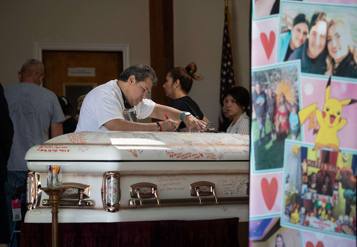 A funeral participant writes a message on the casket as friends and family gather to honor the life of Keyla Salazar, 13, a Gilroy shooting victim, at Our Lady of Guadalupe on Tuesday, Aug. 6, 2019, in San Jose, Calif.