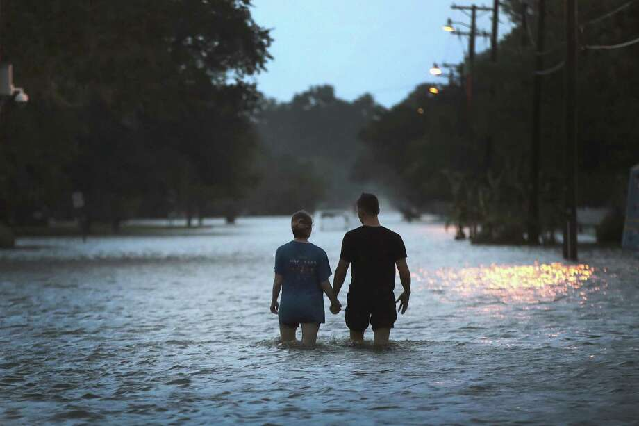MANDEVILLE, LOUISIANA - JULY 13: A couple strolls down Lakeshore Drive along the shore of Lake Pontchartrain after it was flooded in the wake of Hurricane Barry on July 13, 2019 in Mandeville, Louisiana. The storm, which made landfall this morning as a category one hurricane near Morgan City, caused far less damage and flooding than had been predicted. Flash flood watches were issued throughout much of Louisiana and as far east as the Florida panhandle as the storm was expected to dump more than a foot of rain in many areas and up to 25 inches in some isolated locations. Many areas are now expected to get less than half of the original projections. (Photo by Scott Olson/Getty Images) Photo: Scott Olson, Staff / Getty Images / 2019 Getty Images