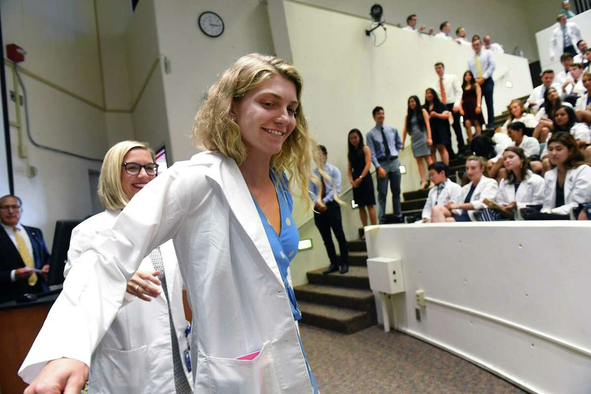 Incoming medical student Chiara Lawrence of Denver receives her white medical coat from second year med student Tatum Weishaupt, left, during the White Coat Ceremony at Albany Medical College on Tuesday, Aug. 6, 2019 in Albany, N.Y. (Lori Van Buren/Times Union)