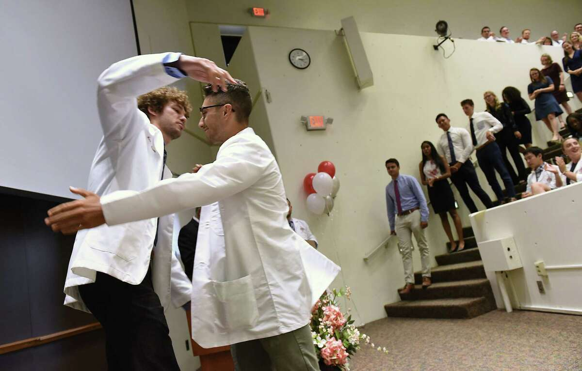 Incoming medical student Spencer Perry of Nassau, N.Y., right, receives his white medical coat from second year med student Mark Wendle during the White Coat Ceremony at Albany Medical College on Tuesday, Aug. 6, 2019 in Albany, N.Y. (Lori Van Buren/Times Union)
