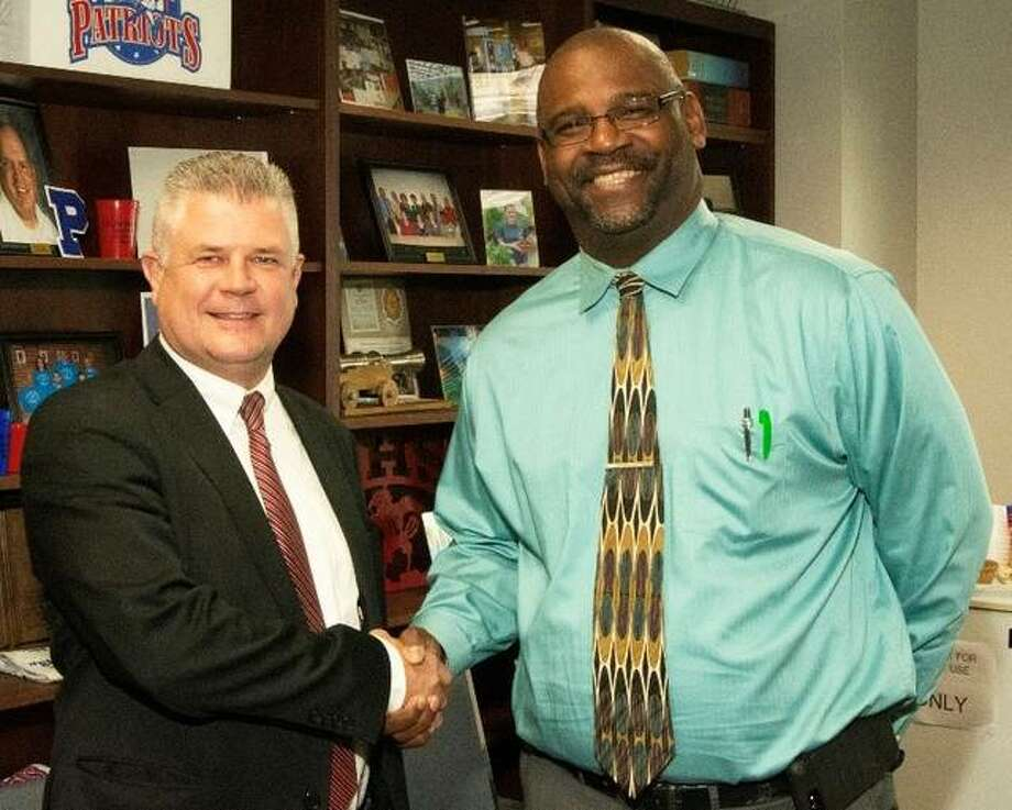 Madison County Regional Superintendent Robert W. Werden, left, welcomes Anthony Smith as principal at the Center for Educational Opportunities School in Troy.