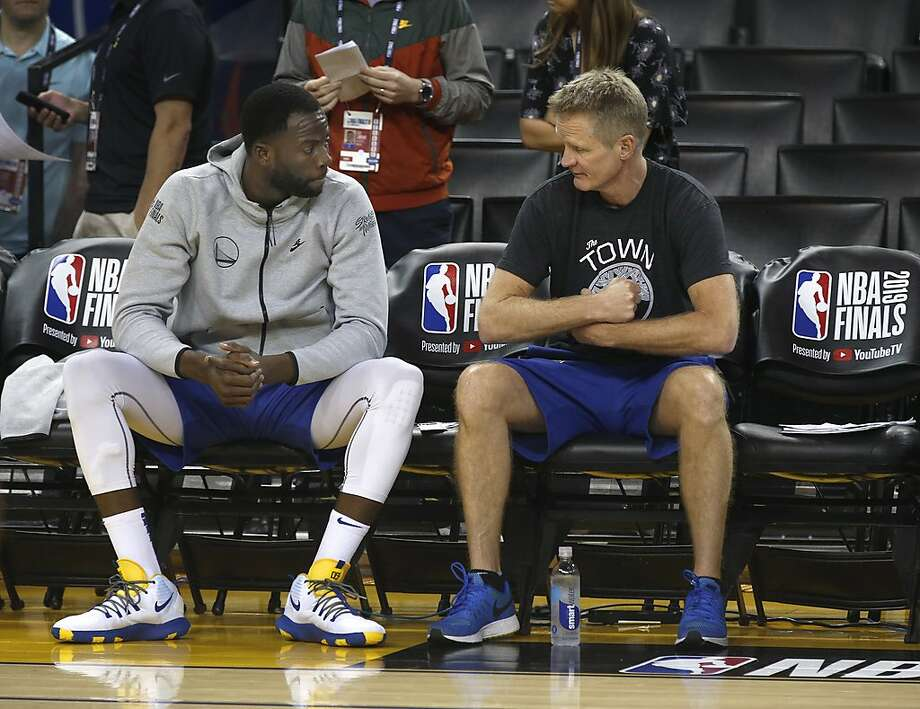 Draymond Green chats with head coach Steve Kerr on the bench during a Golden State Warriors practice at Oracle Arena on June 12, 2019, before Game 6 of the NBA Finals against the Toronto Raptors. Michigan State will honor Green in a jersey-retirement ceremony Tuesday. Photo: Paul Chinn / The Chronicle