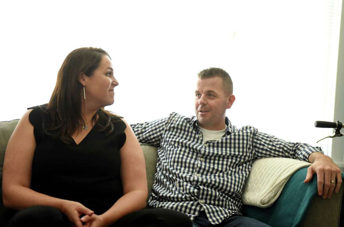 Chelsea and Josh Woodward are interviewed at their home on Monday, Aug. 5, 2019, in Albany, N.Y. Josh lost a hand, toes and part of a foot when the Albany Airport firefighter was stricken with sepsis earlier this year. The family has started a nonprofit called Woodward Strong. (Will Waldron/Times Union)