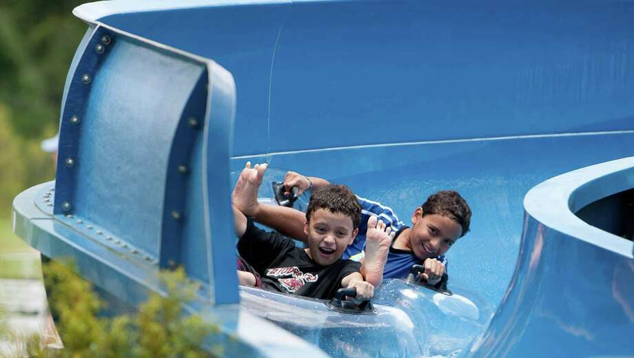Two young boys ride a tube down the slide Sunday at the Rob Fleming Aquatic Center in The Woodlands. The new fee changes at the Rob Fleming pool include: $20 day-use fee for non-residents Monday through Thursday; $30 day-use fee for non-residents Friday through Sunday and holidays; and $15 for resident day-use entry Friday through Sunday and holidays. Photo: Eric S. Swist / Staff Photo By Eric S. Swist / Staff photo by Eric S. Swist