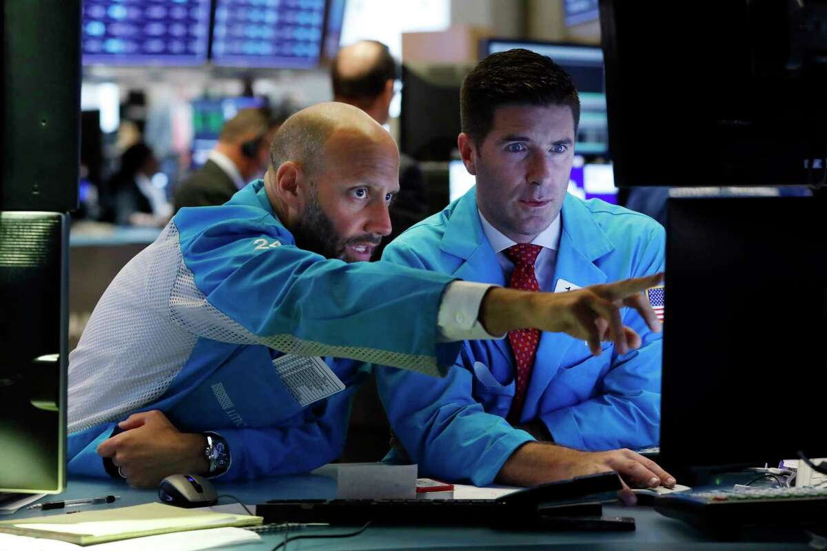 Specialists Meric Greenbaum, left, and Thomas McArdle work on the floor of the New York Stock Exchange, Tuesday, Aug. 6, 2019. Stock markets turned higher on Tuesday as China stabilized its currency after allowing it to depreciate against the dollar in response to President Donald Trump's decision to put more tariffs on Chinese goods. (AP Photo/Richard Drew)