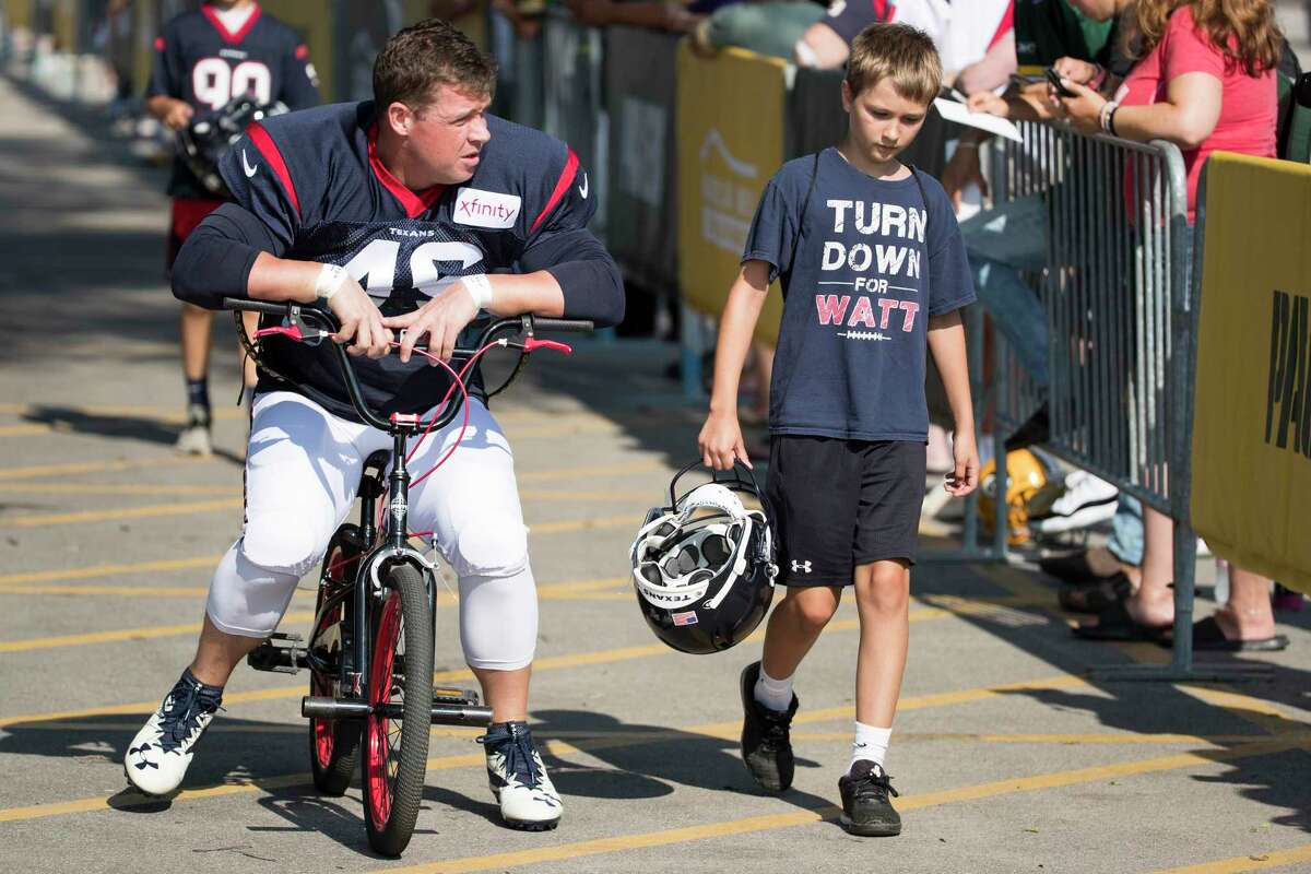 Houston Texans long snapper Jon Weeks (46) rides a bike to a joint training camp practice with the Green Bay Packers on Tuesday, Aug. 6, 2019, in Green Bay, Wis.