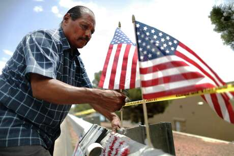 Jose Ozuna installs American flags at a memorial outside the El Paso Walmart, scene of a shooting that left 22 people dead.