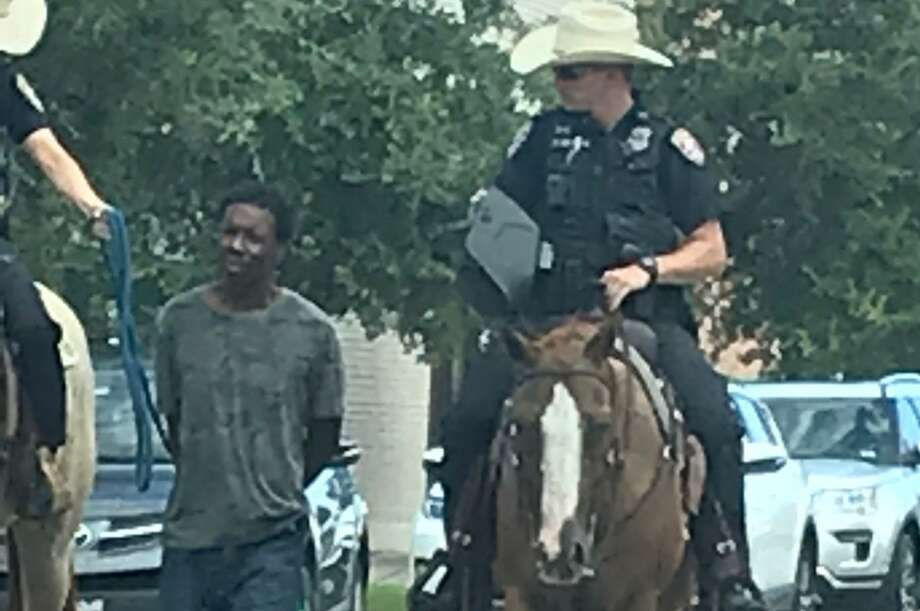 """A man is led to jail by two Galveston police officers on horseback on Saturday. On Monday, a statement attributed to Chief Vernon L. Hale III said, """"Although this is a trained technique and best practice in some scenarios, I believe our officers showed poor judgment in this instance and could have waited for a transport unit at the location of the arrest."""" Photo: Special To The Chronicle"""
